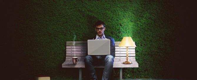 Mann am Laptop auf der Bank
